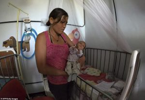 A woman holds her undernourished baby in a hospital in Maracay, Aragua state, Venezuela