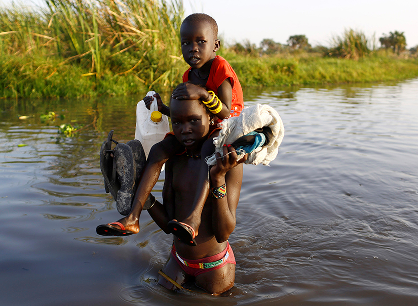 Children cross a body of water in South Sudan in 2017. They are on their way to a food distribution centre. (Siegfried Modola/Reuters)